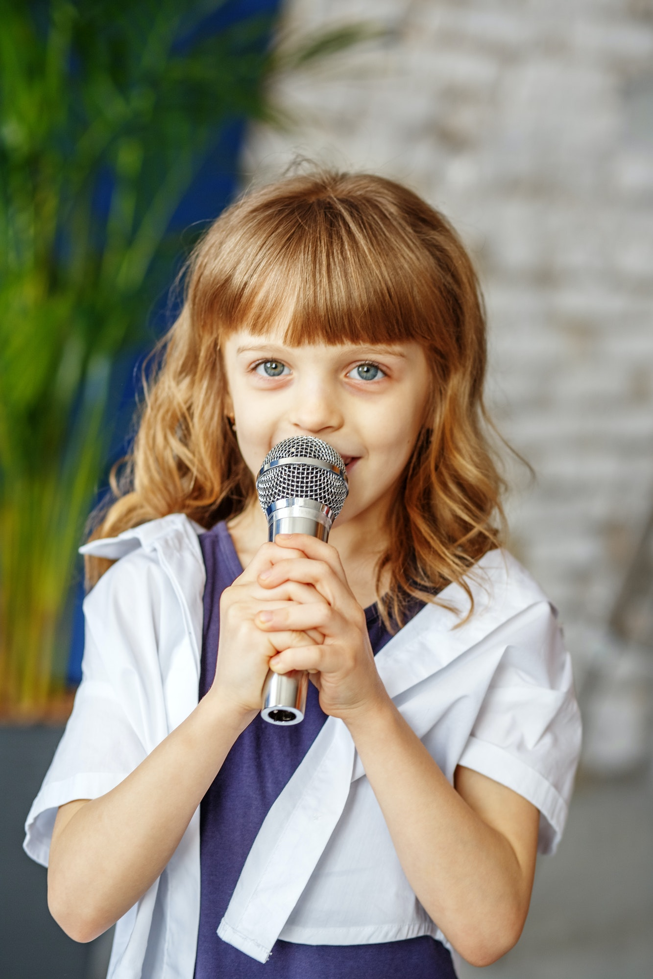 A little beautiful kid sings a song in a microphone. The concept