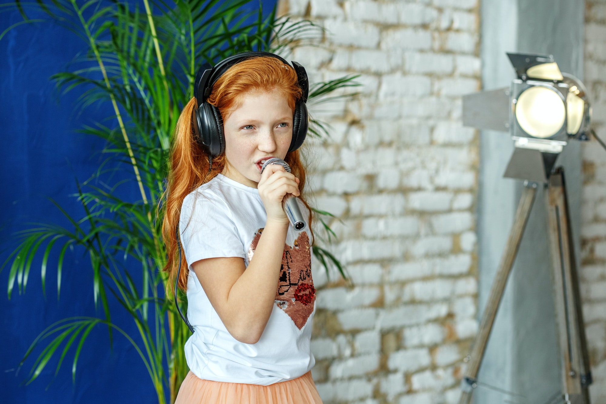 A red-haired child sings a song in a microphone. The concept is